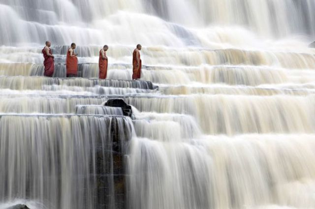 Buddhist monks chant at Pongour Falls, the largest waterfall in Dalat, Vietnam.